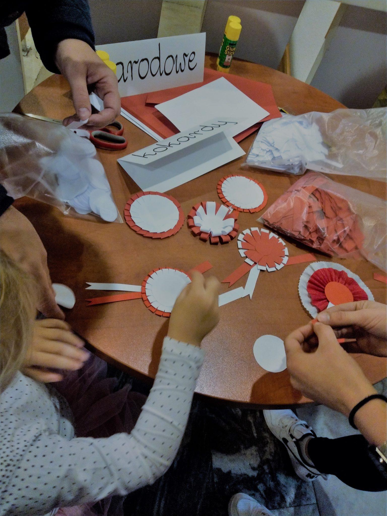 Na zdjęciu dłonie kilku osób wykonujących kokardy narodowe oraz pokazane kilka kokard w trakcie tworzenia.