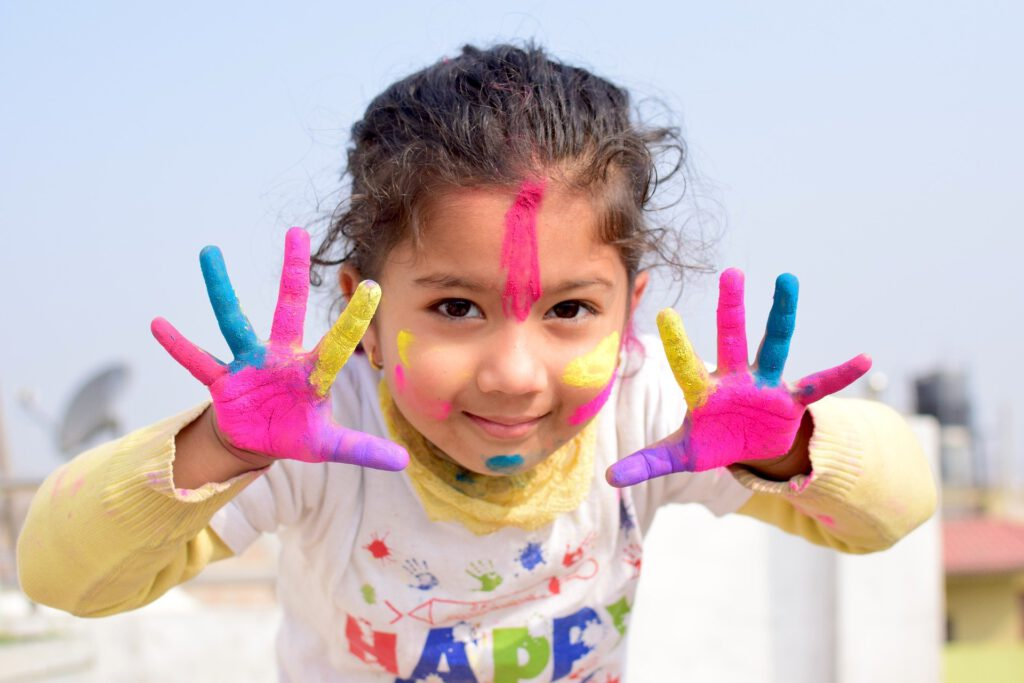 Na zdjęciu dziewczynka pokazująca otwarte dłonie pomalowane farbą na różne kolory: żółty, różowy i niebieski. Twarz dziewczynki również jest pomalowana kolorowymi farbami.